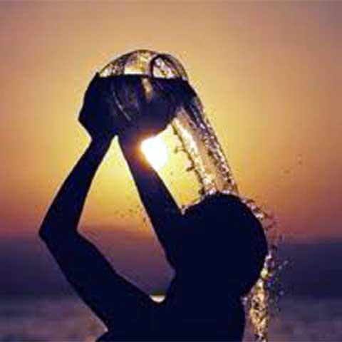 donna si versa acqua in testa al tramonto