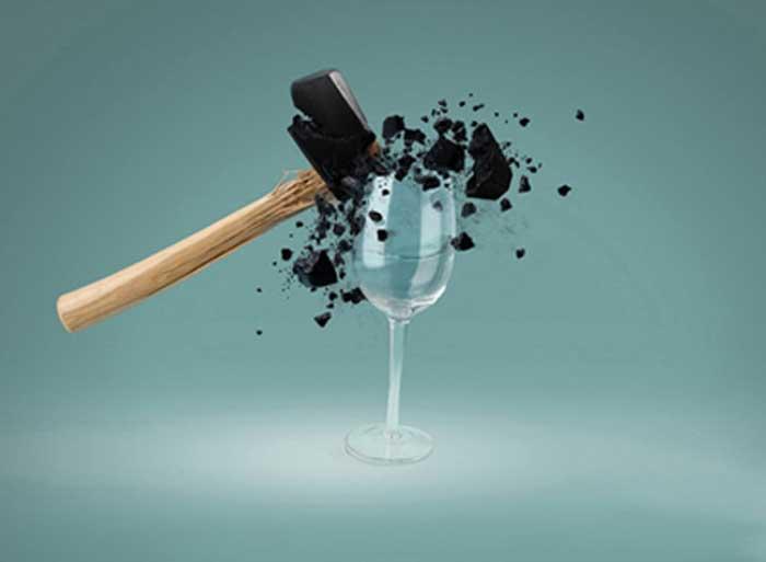 martello di ingrange contro bicchiere cristallino